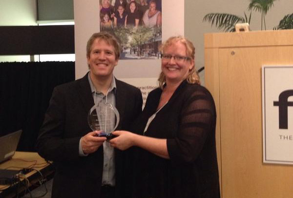 Heather and Charles with the Impact Award.