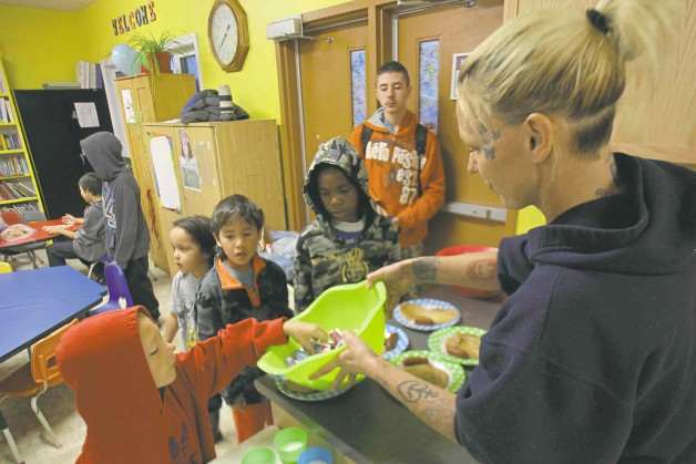 Leah McGuiness hands out food to children for the breakfast program. JOE BRYKSA / WINNIPEG FREE PRESS