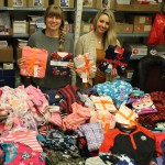 Maiiah Baldwin (left),community investment association, and Hillary Gair, community investment manager, with a fraction of the 2,700+ sets of PJs collected by Manitoba Chiropractors Association members this year.