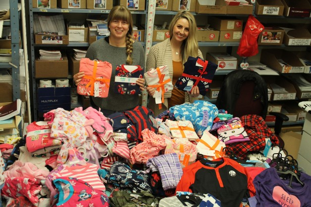 Mariah Baldwin (left), United Way community involvement associate, and Hillary Gair, community involvement manager, with a fraction of the 2,700+ sets of PJs collected by Manitoba Chiropractors Association members this year.