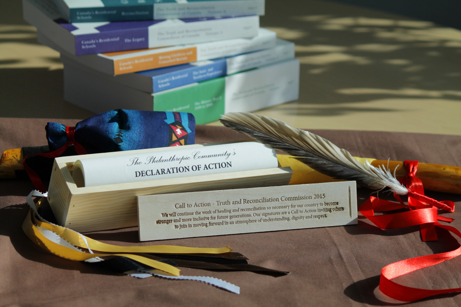 A copy of The Philanthropic Community's Declaration of Action gifted to United Way by The Circle on Philanthropy and Aboriginal Peoples in Canada sits alongside a medicine bag given by Angie Hutchinson. Also shown are a talking stick created and gifted to United Way by former Council for Indigenous Relations chair Christine Cyr and volumes of the TRC report.
