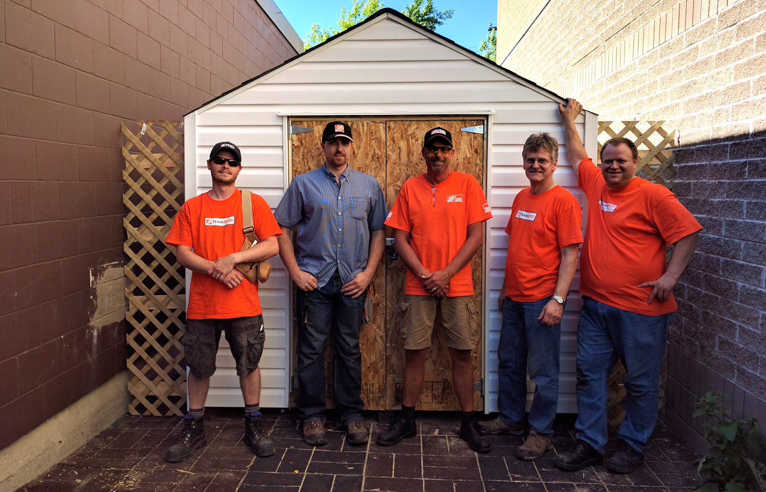 The Home Depot volunteer team stands in front of the finished shed.