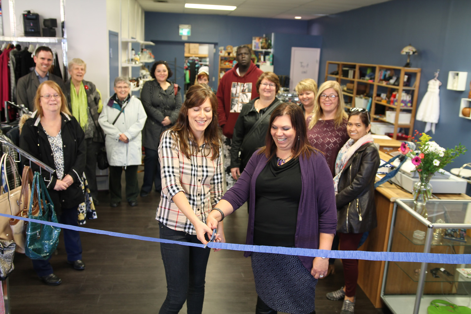 Thrift Shop coordinator Kristy Muckosky, left, and PFSS executive director Rhonda Elias-Penner cut a ribbon to mark the shop reopening.