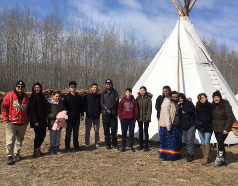 St. John's High School's Aboriginal Youth Leadership Program students stand outside tipi during a sweat lodge outing (Photo provided by Stephanie Midford)