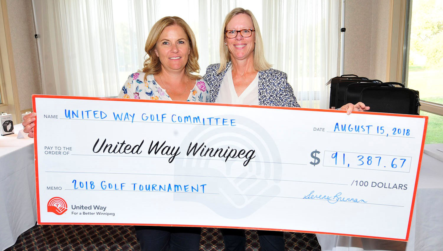 Golf Committee Chair Serena Brennan presents United Way Winnipeg Board Chair Joan Hardy with a cheque for $91,387.67