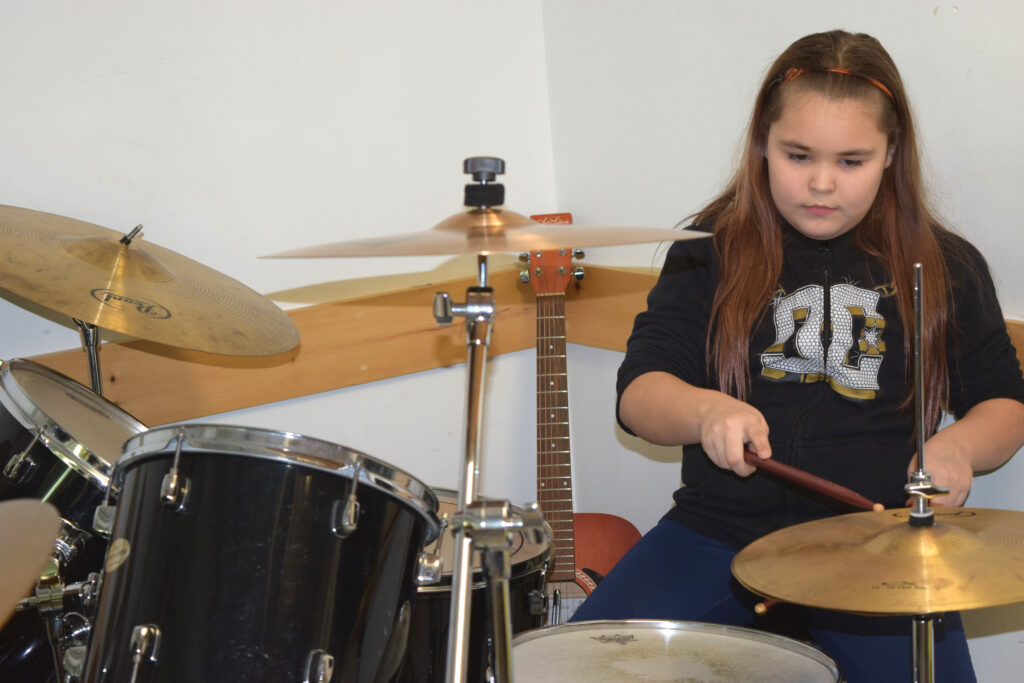 Practicing drumming in the Rossbrook music program.