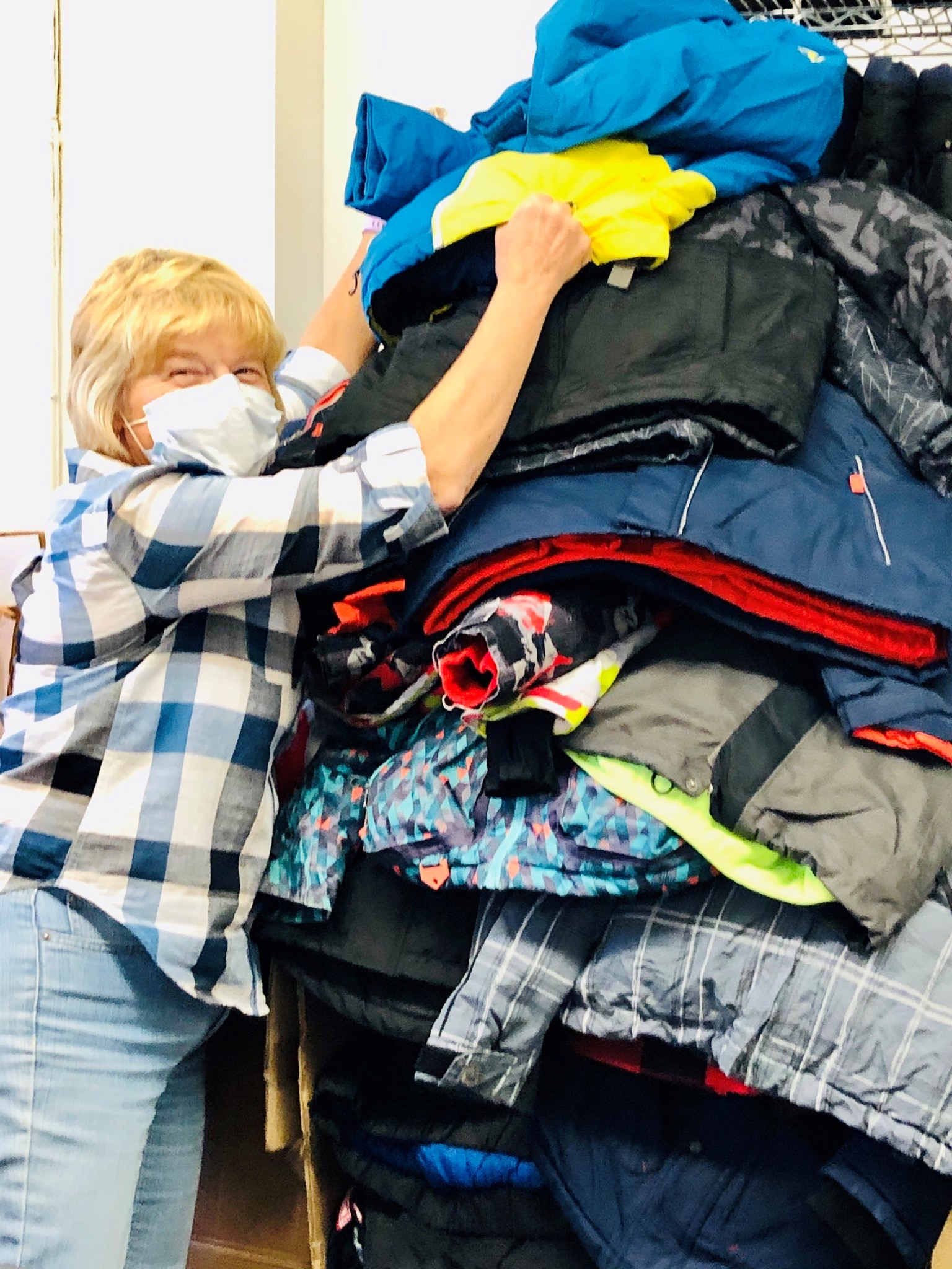 What's Next volunteer sorting a mountain of donated coats.